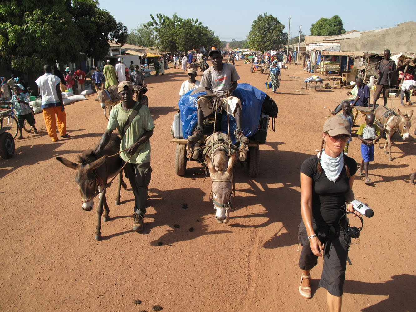 A Short Walk in The Gambian Bush. Image ©Jason Florio - the expedition team walk through a market town in The Gambia, West Africa
