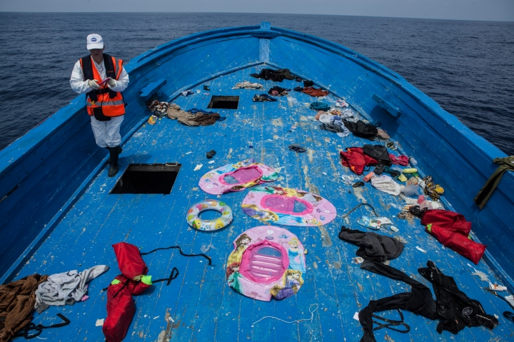 A member of the MOAS team on the the deck, now empty of migrants but strewn with discarded items including three chidrens 'Disney character' paddling pool rafts and a childs rubber ring.