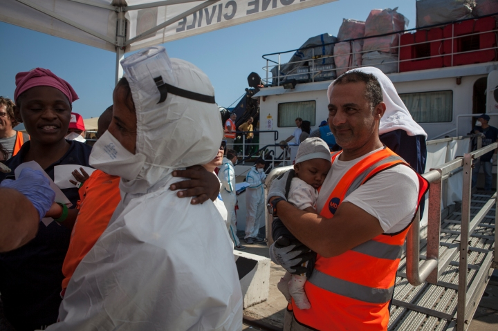 Mimmo one of the members of the MOAS search and rescue team who had help save 4 month old Daryl and his family two days before, carries him ashore at the port of Messina, Sicily.