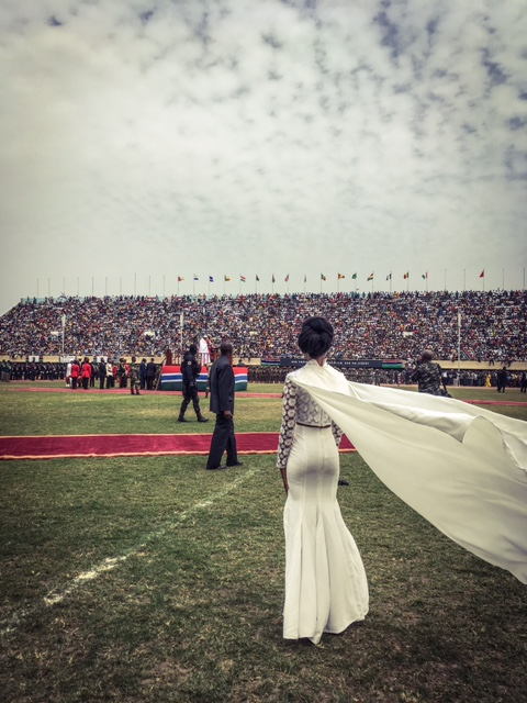 A female singer watches President Barrow being sworn in, as she waits to sing the Gambian National Anthem, Bakau Stadium © Helen Jones-Florio