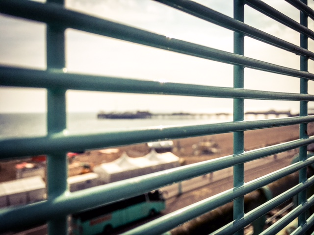 Blurry Brighton Pier seen through the bars of a fence ©Helen Jones-Florio