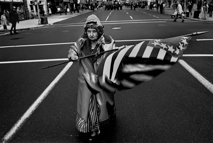 Flag Lady, NYC © Robert Goldstein. Black and white - elderly woman waving large stars and stripes flag in the street