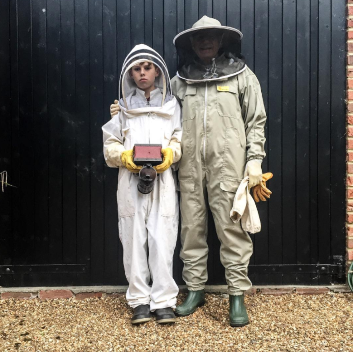 Grandfather Florio with grandson Florio, stand posing in bee-suits, preparing to harvest some Surrey honey, UK © Jason Florio