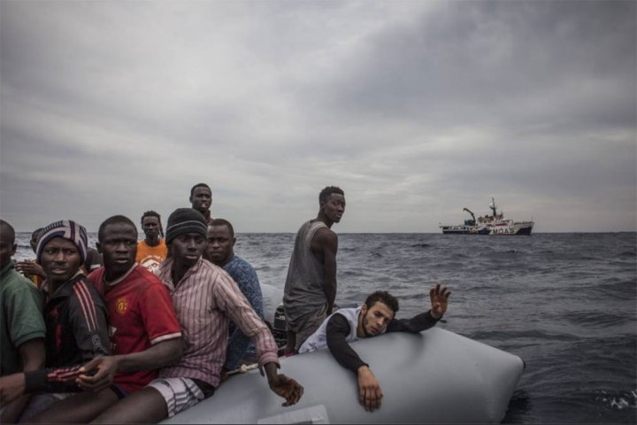 IRIN NEWS - a rubber dinghy, packed with over 120 migrants and refugees, in the Mediterranean Sea - image ©Jason Florio/MOAS