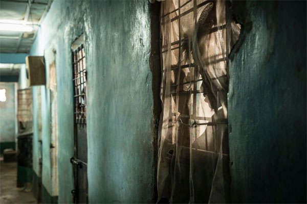 A prisoner looks out from his locked cell, maximum security, Mile 2 prison, Gambia © Helen Jones-Florio