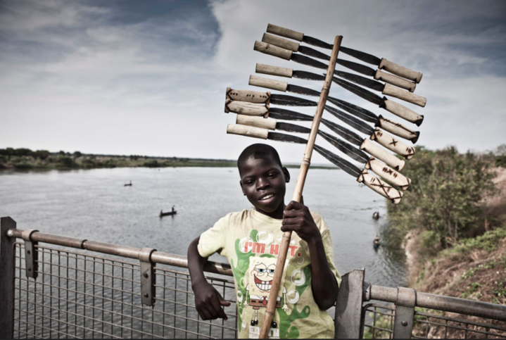 Portrait of a young boy - Knife Vendor' - standing on a bridge in Uganda © Jason Florio