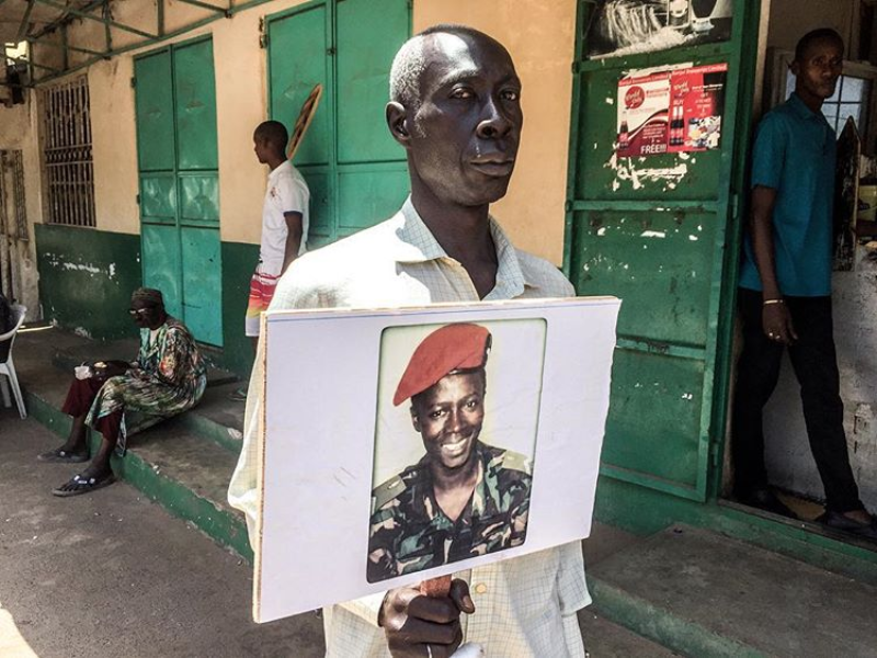 Mr Njie during a vigil, in Banjul, for victims of the Jammeh regime holding a picture of his nephew Nyass who was killed during an attempted coup in 2014 to bring down the dictatorship, Gambia © Jason Florio