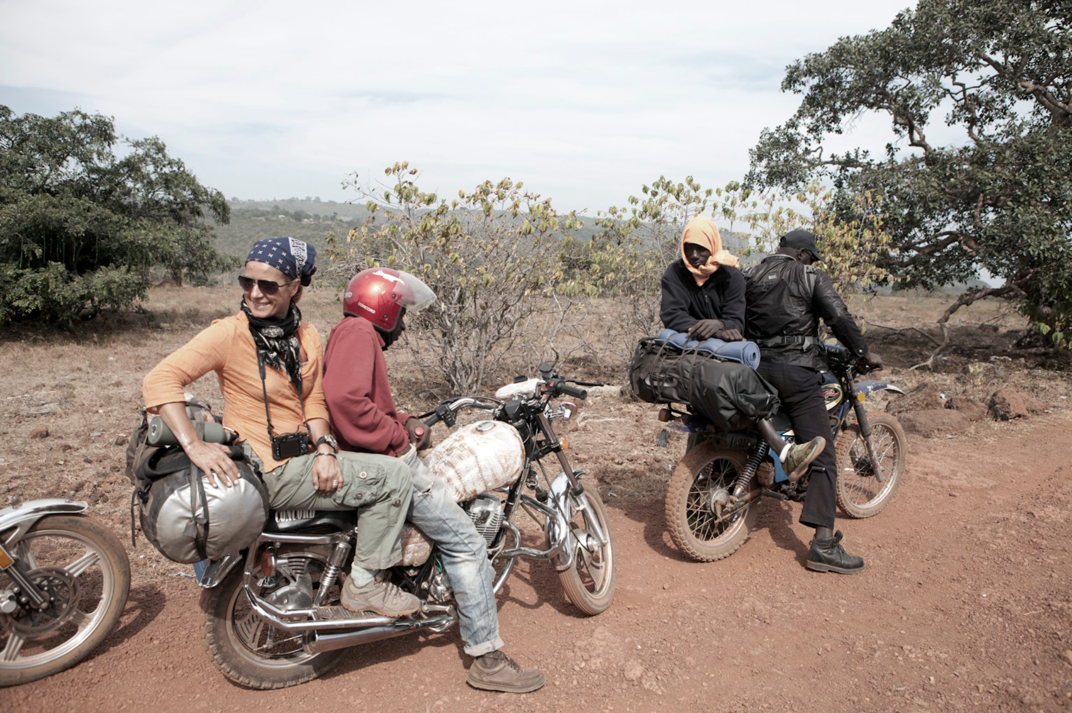 Helen & 'mototaxi' rider, Ebu, and River Gambia Expedition team member, Ebou with his rider – leaving Mali Ville, Guinea-Conakry © Jason Florio