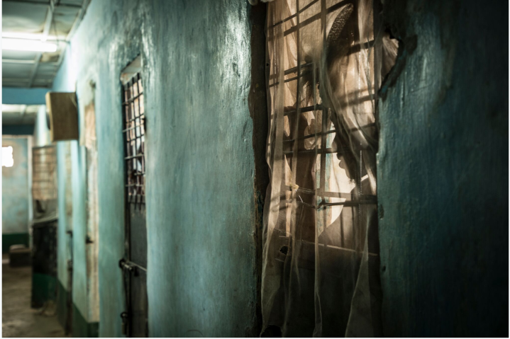 Mile 2 Prison, The Gambia – a prisoner looks out from his cell in the maximum security block– image ©Helen Jones-Florio