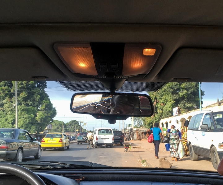 Back in The Gambia! Street scene through the windscreen of a taxi  ©Helen Jones-Florio
