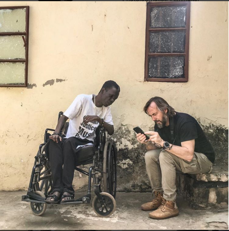 Jason Florio, with Yusepha Mbye, who was shot in the back by security forces in 2000 student protest - making #Portraits4PositiveChange #Gambia - image, Gambia © Helen Jones-Florio