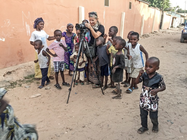 Helen Jones-Florio filming in The Gambia, surrounded by small children © Jason Florio