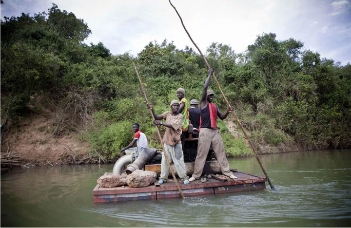 Young men on a float taking a generator to a banana plantation on the River Gambia, Senegal, West Africa © Jason Florio