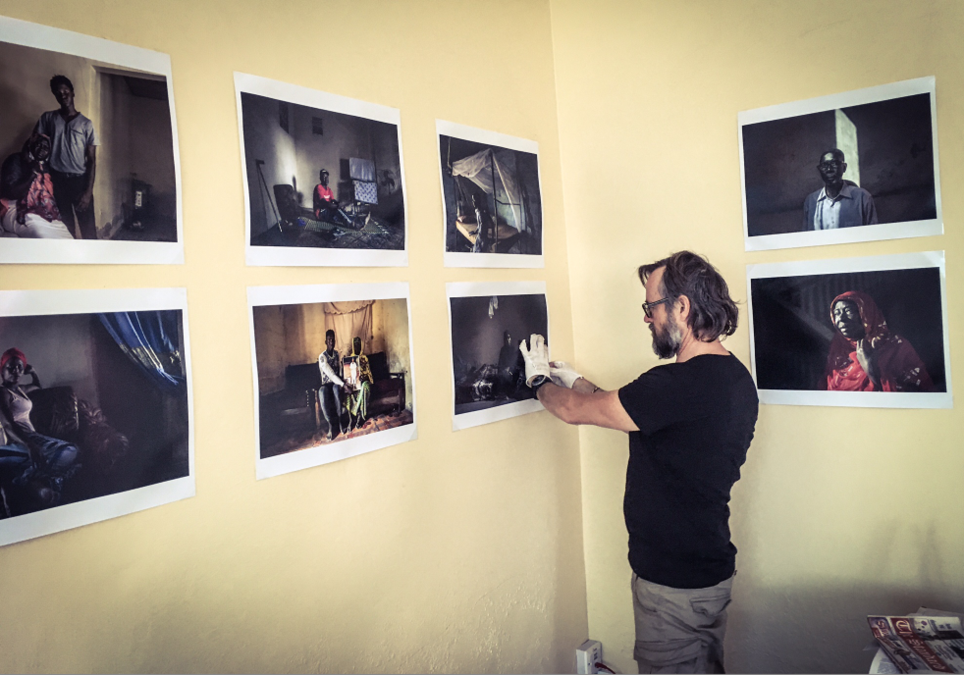 Photographer, Jason Florio, installing the exhibition 'Portraits to Remember' victims and resisters  © Helen Jones-Florio, the gambia