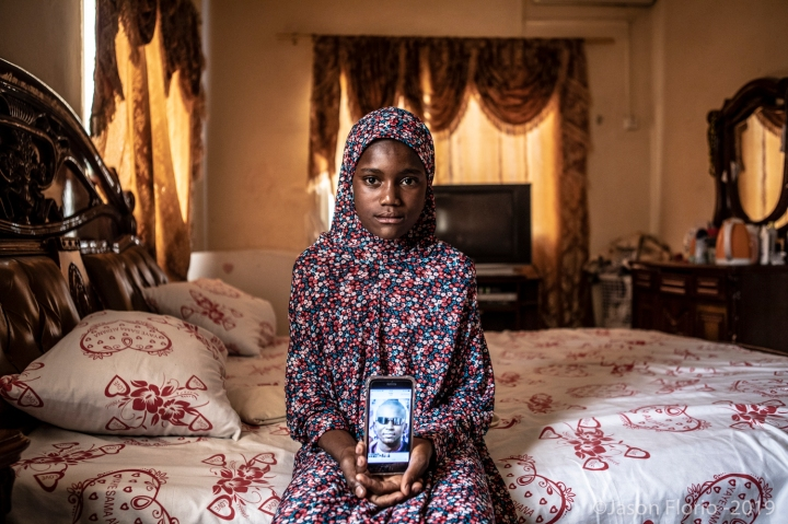 Gambia - victims and resisters: portrait of Bintu Tunkara, daughter of murdered Gambian Lamin Tunkara, holding the only photo she has of him on her mothers cell phone ©Jason Florio