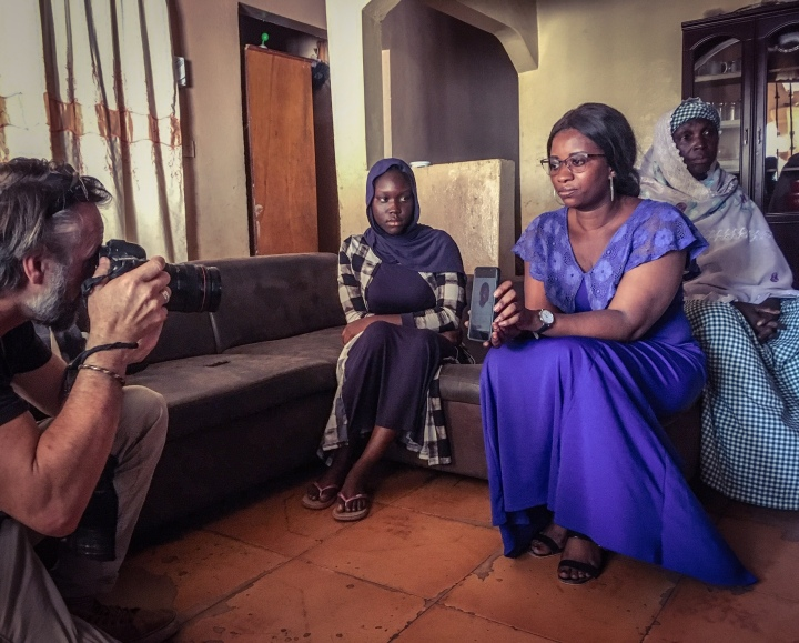Photographer, Jason Florio, makes a portrait of Awa Barrow, holding a phone picture of her husband, Omar Barrow, who was shot dead by Gambian security forces, on April 10, 2000, during student protests in The Gambia. Omar's daughter, Fatou, looks on. She was only a few months old when her father was killed. His mother sits in the background. Image ©Helen Jones-Florio
