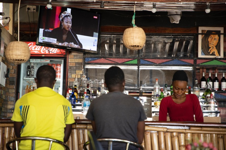Young Gambian men watch the TRRC on TV in a bar as Fatou 'Toufah' Jallow testifies, The Gambia. Image © Jason Florio