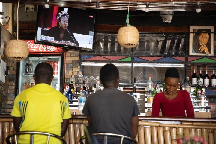Young Gambian men watch the TRRC on TV in a bar as Fatou 'Toufah' Jallow testifies, The Gambia. Image © Jason Florio