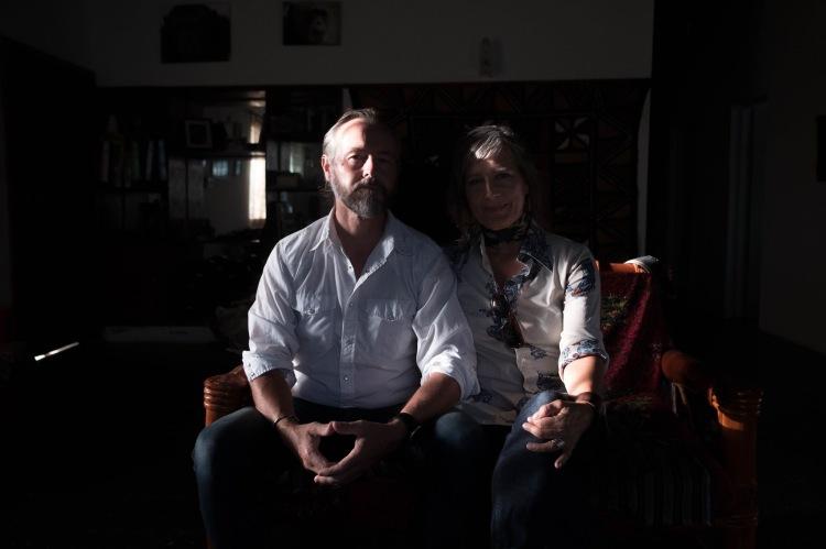 Photographers  & Filmmaker, Jason Florio & Helen Jones-Florio  pose for a photo in a semi-darkened room