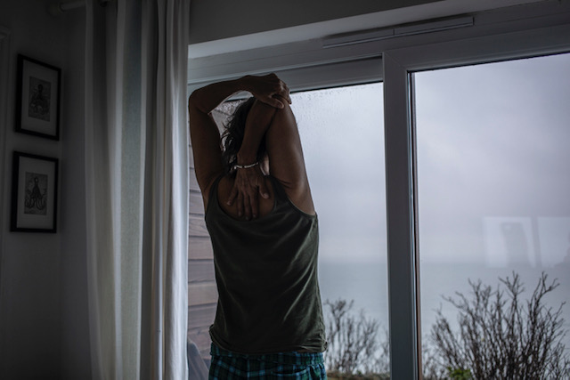 (self) Isolation - image © Jason Florio - a lone woman stretches in the early morning, looking out the window at the sea, Cornwall, UK