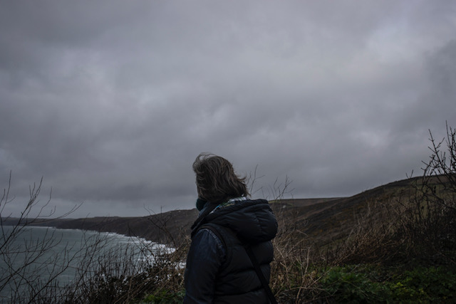 (self) Isolation - image © Jason Florio - a lone woman looks out at the ocean from a cliff top, Cornwall, UK