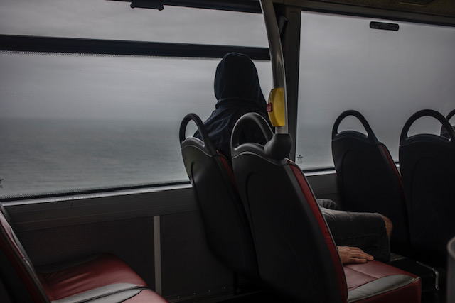 Isolation - images ©Jason Florio - man sits on the the top deck of a bus, overlooking the sea, Cornwall, UK