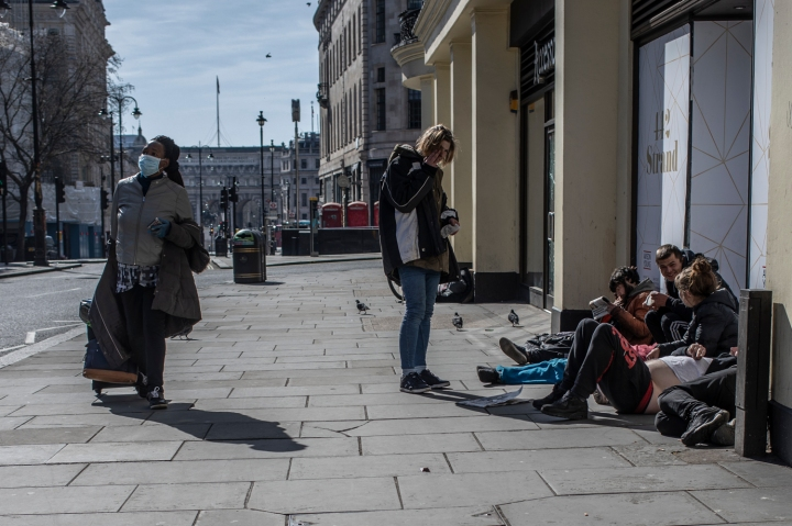 COVID 19 London lockdown. Homelessness - A woman an wearing a face mask walks past a group of homeless people, in a semi-deserted London street ©Jason Florio
