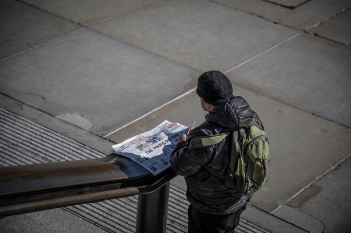 COVID 19 London lockdown. Homelessness-A lone man reads the newspaper in a deserted Trafalgar Square, London. Image © Jason Florio