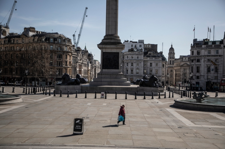 COVID 19 London lockdown. Homelessness - A lone homeless man walks across a deserted Trafalgar Square, London. Image ©Jason Florio