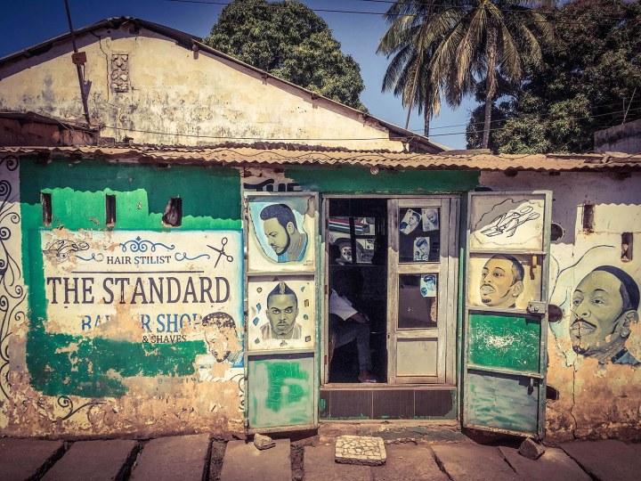 #GambiaDoors: Doors & Storefronts, The Gambia, West Africa - barber shop storefront showing hand-painted hairstyles. Image © Helen Jones-Florio