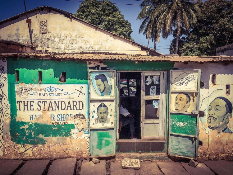 #GambiaDoors: Doors and Storefronts of The Gambia, West Africa - barber shop storefront showing hand-painted hairstyles. Image © Helen Jones-Florio