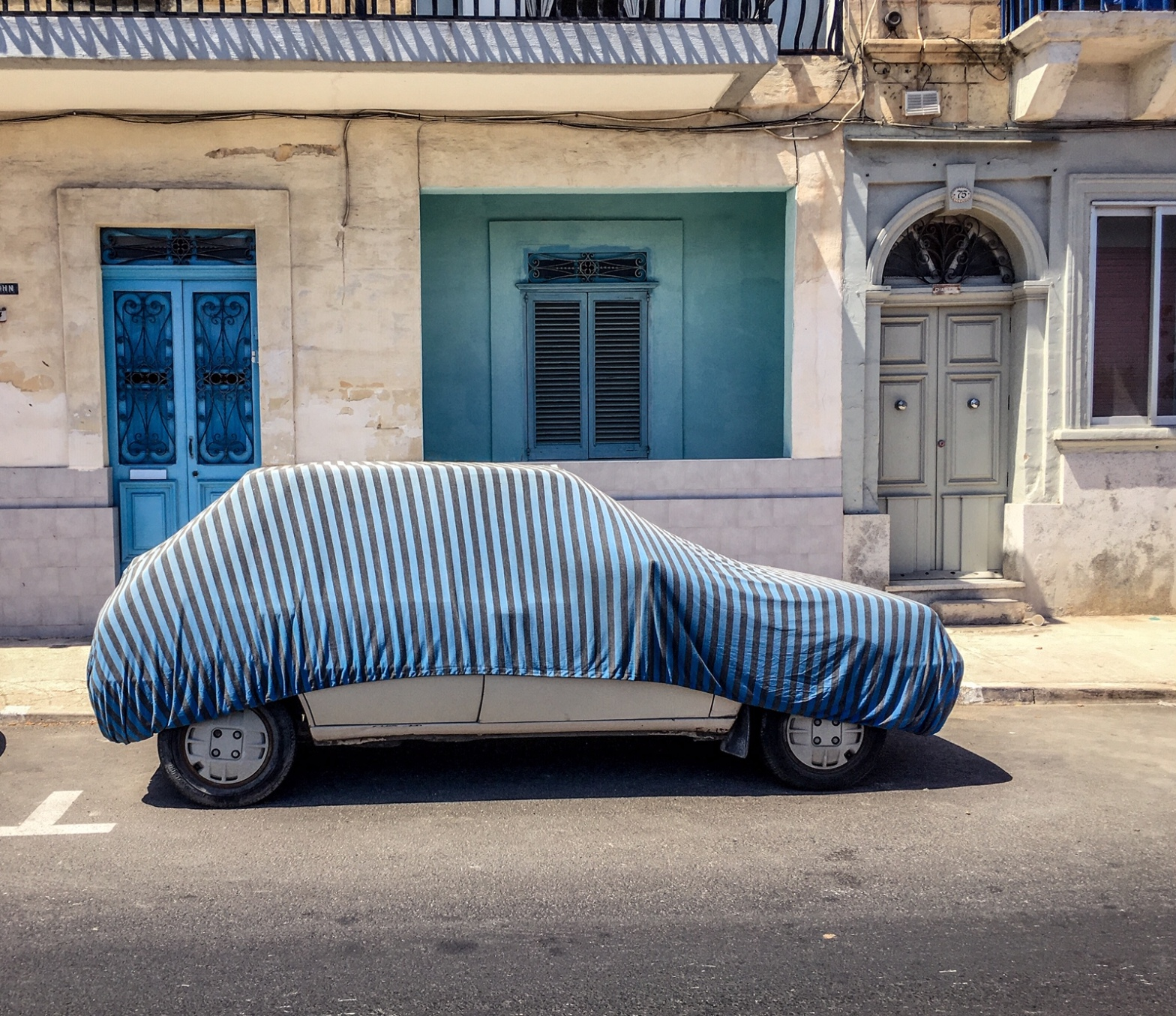 A car with blue striped cover, against blue house and doors, Malta. Image © Helen Jones-Florio