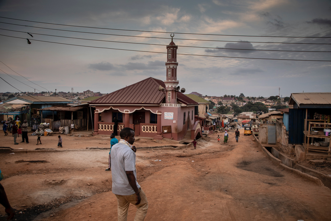 A man walks down the street towards the mosque, Kumasi, Ashanti Region, Ghana. Image ©Jason Florio