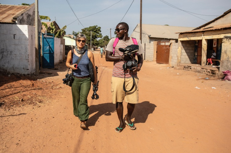 Helen Jones-Florio, and Madi Sonko, on location walking through the streets of urban Gambia, West Africa. Image ©Jason Florio