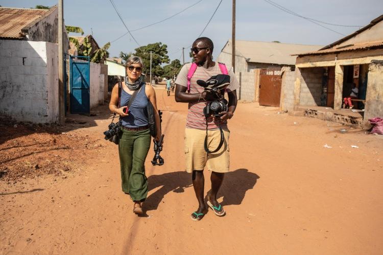 Helen Jones-Florio, and Madi Sonko, on location walking through the streets of urban Gambia, West Africa. Image ©Jason Florio