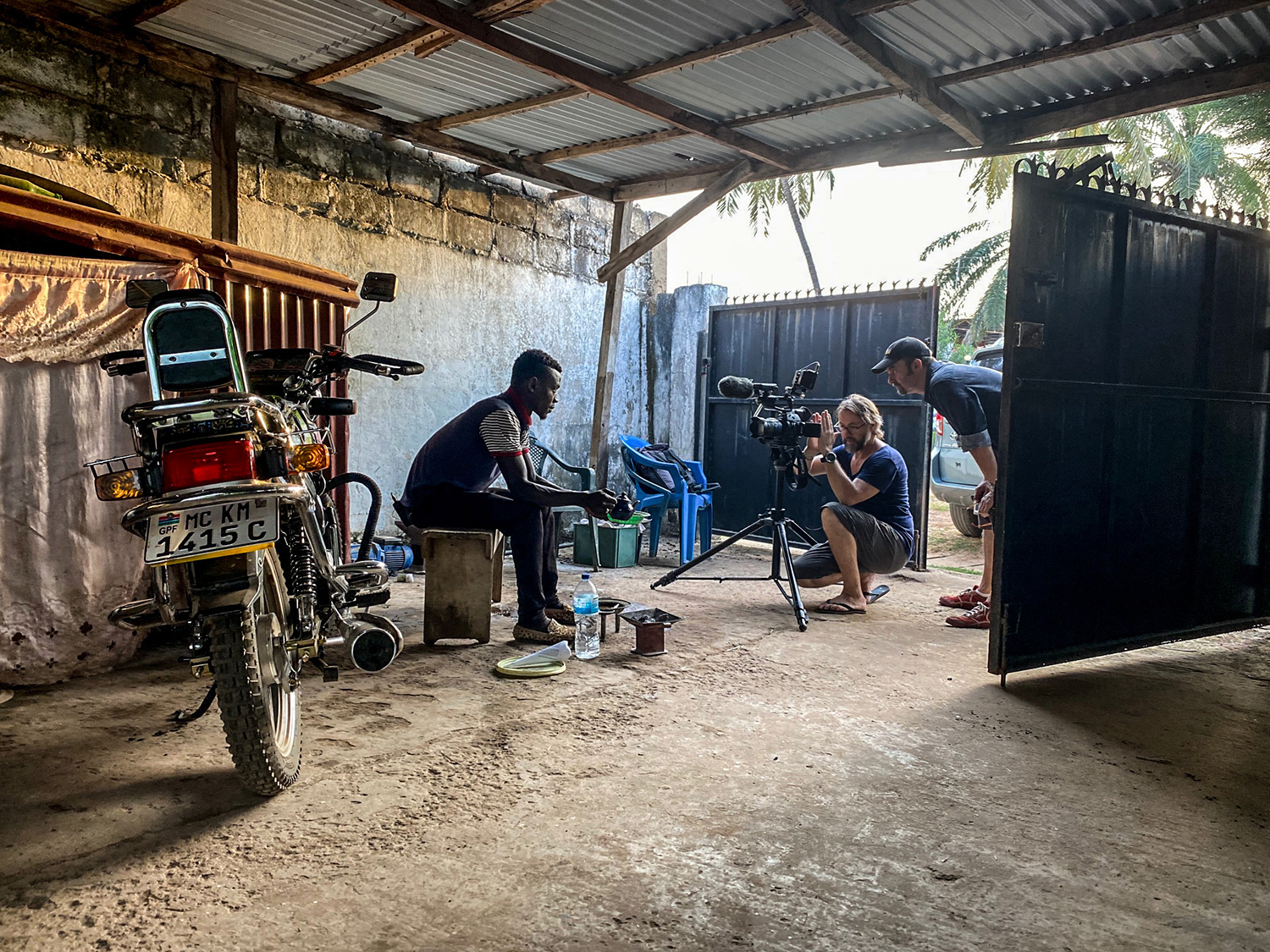 Photographer, Jason Florio, films an interview with a young Gambian man who is sitting in by an open gate, making attaya tea, next to a motorcycle, The Gambia, West Africa , Image ©Helen Jones-Florio