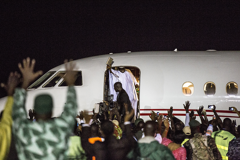 Ex President of The Gambia, Yahya Jammeh, waves goodbye to followers who came to see him off from Banjul airport as he leaves for exile in Equatorial Guinea. Image ©Jason Florio
