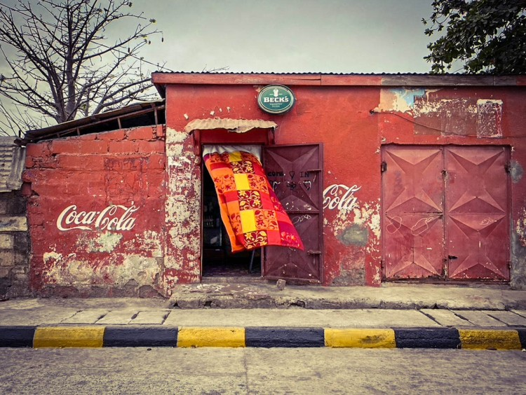 #GambiaDoors - a brightly coloured curtain blows in the doorway of a local bar, a Becks beer sign above the door, painted red with Coca Cola written on the wall, Banjul, The Gambia ©Helen Jones-Florio