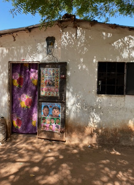#GambiaDoors - the front of a local barber shop, with a patterned curtain in the doorway and posters depicting haircuts. Image ©Helen Jones-Florio
