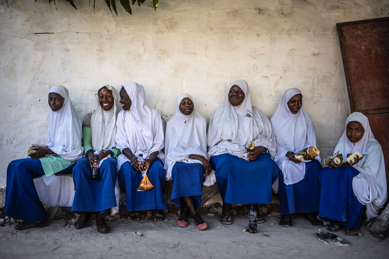A group of Koranic school girls sitting together on a bench against a wall, smiling and laughing, The Gambia, West Africa. Image ©Helen Jones-Florio