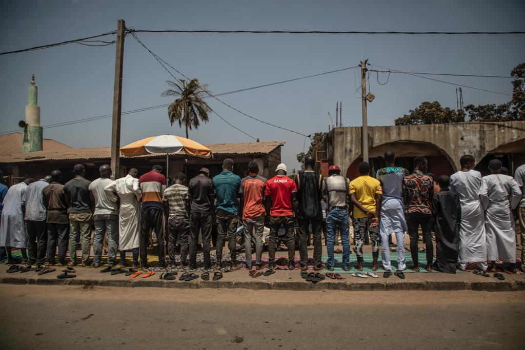 Documenting Gambia - a line of muslim men doing Friday prayers on the side of an urban road, The Gambia, West Africa. Image ©Jason Florio
