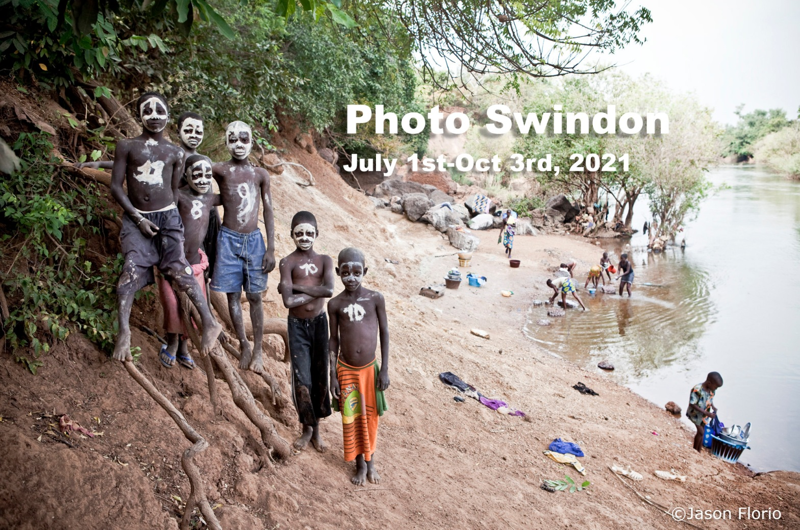 Photo Swindon International Photography Exhibition - 1st July-3rd October, 2021. Boys with painted faces stand looking at the camera, by the River Gambia, West Africa - advertisement for Photoswindon photo exhibition. Image ©Jason Florio