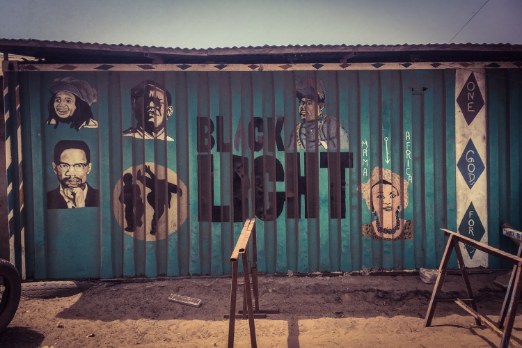 #GambiaDoors - the front of a shipping container, hand painted with faces, and the words'Black Light, Tanji, The Gambia. Image ©Helen Jones-Florio