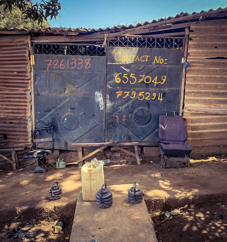 #GambiaDoors - blue metal doors of a workshop, with hand painted telephone numbers, and an old car seat standing outside the closed doors, Bakau, The Gambia. Image ©Helen Jones-Florio