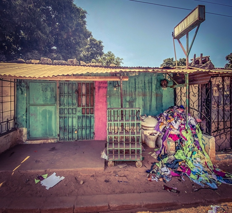 #GambiaDoors - the closed frontage of a tailor shop with a pile of remnant fabric, and an old toilet, Bakau, The Gambia. Image ©Helen Jones-Florio
