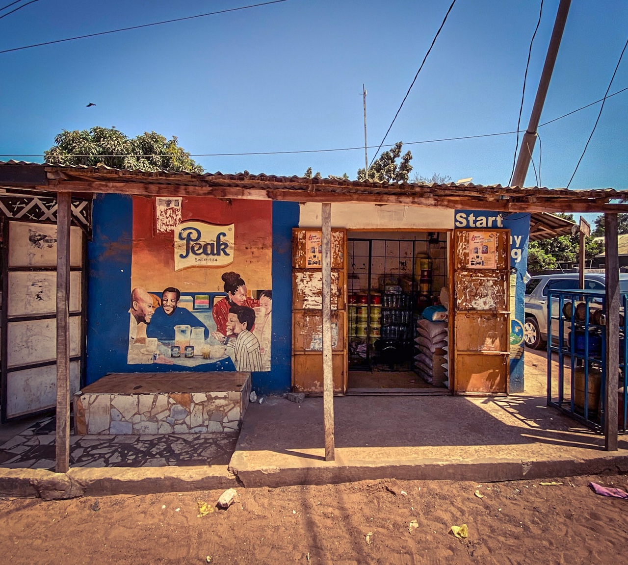 #GambiaDoors - a local shop, with a hand painted frontage, with a mural of a family sitting around the breakfast table, advertising 'Peak Milk', Bakau, The Gambia. Image ©Helen Jones-Florio