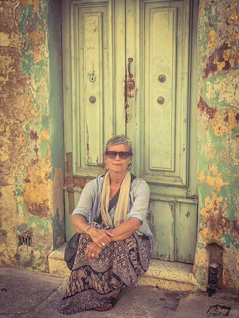 Helen Jones-Florio, sitting on the doorstep of an abandoned house, Malta. Image by Jason Florio