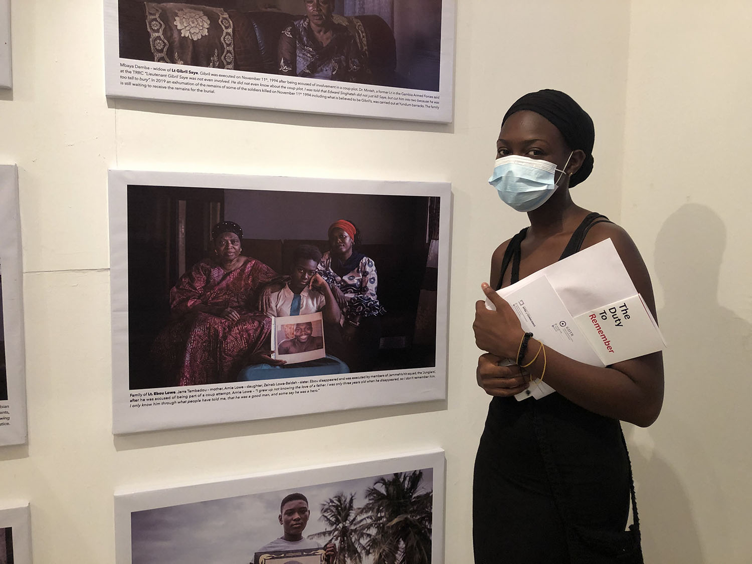 Opening of 'Memory House', The Gambia, West Africa. A young Gambian woman stands in front of a portrait of herself with her family. Images ©Jason Florio & Helen Jones-Florio from 'Gambia - victims, and resisters'